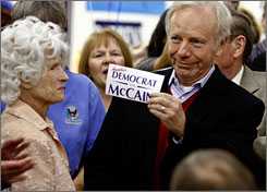 "Sen. Joe Lieberman, I-Conn., holds up a sticker that reads ""Another Democrat for McCain"" during a stop at a call center with Republican presidential nominee John McCain and his mother Roberta McCain, pictured left,  on Nov. 4 in Albuquerque."