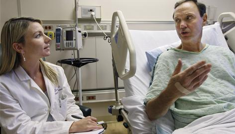 Dr. Alexis Dunne talks with patient Michael McCoy, right, at Northwestern Memorial Hospital in Chicago, where she plans to be a primary care doctor. In a      September survey, only 2% of nearly 1,200 fourth-year medical students said they plan to work in general practice and a new survey shows many current primary care physicians plan to retire soon.