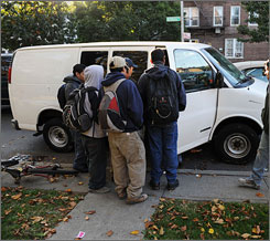 Immigrant men crowd by the van of a potential employer who might hire them for the day in the early morning on Oct. 17 on a street corner in Brooklyn. The men wait for vans from construction, rubble cleaning companies and other services that hire day laborers. In tough financial times, the work has slowed for these immigrants.