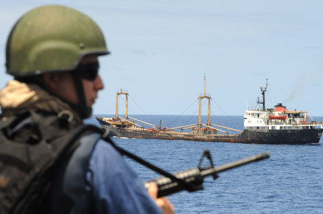 A Canadian sailor guards a U.N. World Food Program ship bringing relief into Mogadishu, Somalia, in September. With piracy on the rise, more nations are gearing up to fight back.
