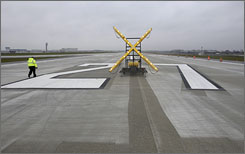 A worker at Chicago's O'Hare International Airport walks along a new runway on Nov. 12 set to open on Thursday.