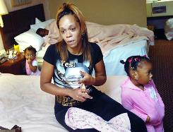 Rockell Joseph, her husband, Rafeal, in background, and their six children have lived in a motel since their FEMA trailer park closed last month.