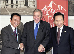 U.S. President George W. Bush, center, poses with his South Korean counterpart Lee Myung-bak, right, and Japanese Prime Minister Taro Aso on Saturday before their bilateral meeting on the sidelines of the Asia-Pacific Economic Cooperation (APEC) summit in Lima.