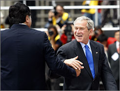 U.S. President George W. Bush, right, is greeted by Peruvian President Alan Garcia as Bush arrives at the Ministry of Defense Convention Center for the first meeting of the Asia-Pacific Economic Cooperation (APEC) summit in Lima on Saturday.