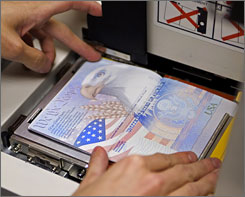 A U.S. government official places a new U.S. passport with an embedded electronic chip into a book printer.