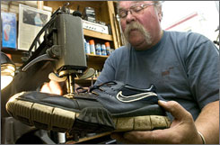 Steven Hopkins, owner of Onion River Cobbler in Winooski, Vt., fixes the stitching on a pair of sneakers recently.
