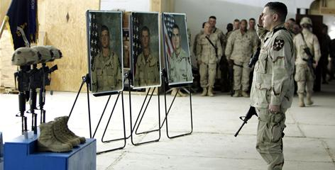 Then-Col. Gary Patton salutes during a service for Staff Sgt. Thomas Vitagliano, Pfc. George Geer and Pfc. Jesus Fonseca. The men died Jan. 17, 2005, in Ramadi.