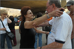 Oakridge Mobile Home Park manager Ginny Harmon hugs resident John Hackney before going to search for anything left at the park. Almost 500 units were destroyed by fire nearly two weeks ago.