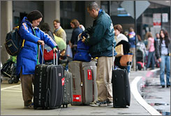 Travelers gather their luggage Tuesday before checking in for a flight at San Francisco International Airport.