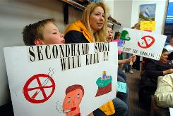 Joey Cifelli, with mom Paula, a casino dealer, holds a sign supporting a smoking ban in Atlantic City, in 2007. After much back and forth, smoking is allowed at this time. A U.S. decline in smoking is largely credited with the first drop in cancer death rates and the number of cancer cases.