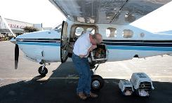 """Jon Wehrenberg, co-founder of Pilots N Paws, unloads carriers full of shelter dogs in Greensboro, N.C. """"Pilots love to fly. I believed that if we created a means for them to discover situations where they could fly and also save animals, many would do it,"""" he said."""