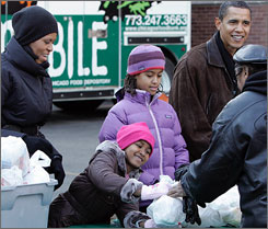 President-elect Barack Obama, right, and his family, left to right, wife Michelle and daughters Sasha and Malia, give out food at St. Columbanus Parish and School in Chicago on Wednesday.
