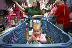 Jessica Luu, left, looks for deals as her friend's baby, Kaylee Oliver, inspects a toy in the shopping cart in a store in Selma, Texas.
