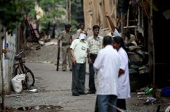 A forensic team works on Sunday outside Mumbai's Hebrew center, Nariman House. Coordinated terrorist attacks that began on November 26 targeted a railway station, two hotels, a hospital and cafe as well as the Jewish center, leaving at least 174 people dead, including 22 foreigners.