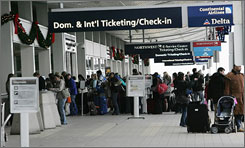 Holiday travelers line up Sunday at Detroit Metropolitan Airport check-in counters.