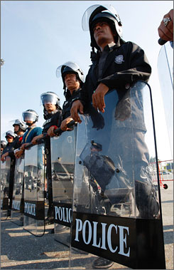 Police in riot gear gather outside of the itnernational airport in Bangkok, Thailand, on Monday.