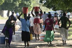 Women carry water in buckets as others carry empty buckets towards the underground water source, after water was cut in Harare, Zimbabwe, on Monday. Water in the capital was cut due to shortage of purification chemicals as Zimbabwe battles with a cholera outbreak which is thought to have left hundreds dead.