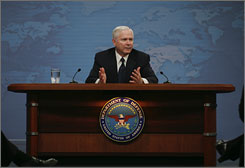 Defense Secretary Robert Gates, seen here talking to reporters at the Pentagon on Tuesday, says the United States is looknig to accelerate troop withdrawal from Iraq. Gates will stay on in his role under President-elect Barack Obama.