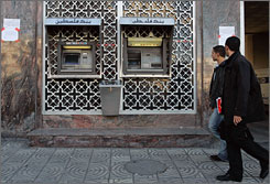 The World Bank warns that cash has been so limited at banks in Gaza that they may collapse. Here, Palestinians walk past a cash machine of the Bank of Palestine branch in Gaza on Thursday.