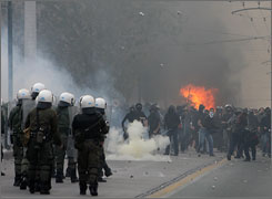 Protesters throw stones at riot police during clashes in Athens.