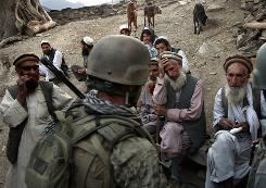 "Village elders in Korengal Valley, Afghanistan, speak with a U.S. Marine as Afghan forces search for weapons. Behind the scences, field anthropologists offer the U.S. military a ""deep perspective"" of the various Afghan cultures. But some say the science has been used to identify targets."
