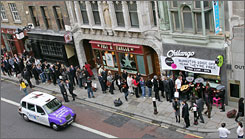 "Londoners form a ""queue"" outside a restaurant.  A consumer watchdog group says Britons should act like Americans and demand better service."