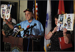 Alexander Santora and his wife, Maureen, family members of 9/11 victims, hold up photos of New York City firefighters killed onSpet. 11, 2001, during a news conference Monday at Guantanamo Bay, Cuba.