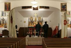 The Rev. Thomas Abraham, left, and Shaju Maninalethu, stand in front of the altar at St. Thomas Syrian Orthodox Knanaya Church after the shooting in Clifton, N.J., on Nov. 24. The Knanaya Church is a Christian sect with strict inter-marriage customs, so many members know each other regardless of where they are in the world.