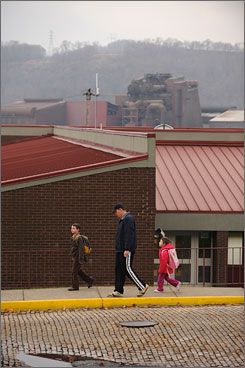 Nathan List walks his children, Brodie, 7, and Payton, 4, to Midland Elementary-Middle School in Midland, Pa., where air monitoring found high levels of chromium and manganese.