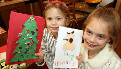 "Dani Verrue, 4, left, and Jacqui, 7, create new Christmas cards from old at their home in Sammamish, Wash. The girls also will be caroling at a senior center and selecting toys for needy kids. ""We want them to feel the spiritual side of the holiday,"" says their mother, Diana Verrue."