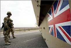 British soldiers keep watch as tank drives by in Basra, Iraq, in December 2007.