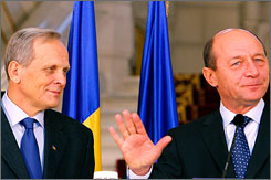 Theodor Stolojan, left, looks on in Bucharest, Romania, shortly after Romanian President Traian Basescu, right, designed him the country's new prime minister.