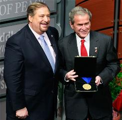Rick Warren, founder of the Saddleback Valley Church, presents President Bush with the International Medal of PEACE during the Saddleback Civil Forum on Global Health at the Newseum in Washington, D.C., Dec. 1.