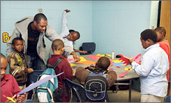 Boys and Girls Club Program Assistant Eric Gaffney, left, works with some after-school kids during an Art program at the club in Charleston S.C. Dec. 5. Several Boys & Girls Clubs in South Carolina announced plans to close Friday.