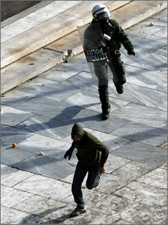 A riot policeman in Athens, chases a demonstrator on Friday.