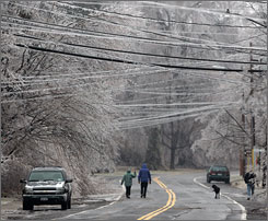 An ice storm in New England and Upstate New York cut off power to more than a million customers. Here, pedestrians brave an ice-covered street in Kinderhook, N.Y.