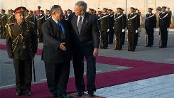 President Bush and Iraqi President Jalal Talabani walk past an honor cordon Sunday as the president arrives at Salam Palace in an unannounced visit to Baghdad.