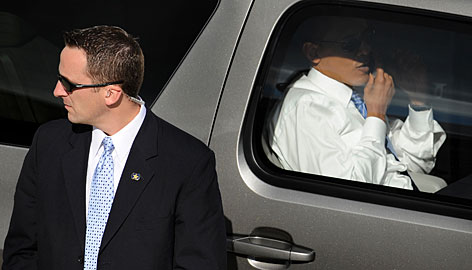 Then-presidential candidate Barack Obama sits inside his motorcade SUV in October in St. Louis after speaking to 100,000 supporters, as a security agent scans crowd.