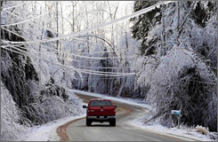 A truck makes its way along a road lined with ice-covered trees on Sunday in North Berwick, Maine.