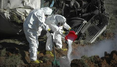 Environmental workers treat a sulfuric acid spill on U.S. Highway 71 near Texarkana, Ark.