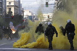 Riot police walk through yellow smoke from a flare thrown by rioters at a demonstration in central Athens on Thursday. More than 7,000 people took part in the protest against the Dec. 6 police killing of a teenager, which has sparked Greece's worst rioting in decades. Friday brought more protests, and youths attacked the French Institute in Athens.