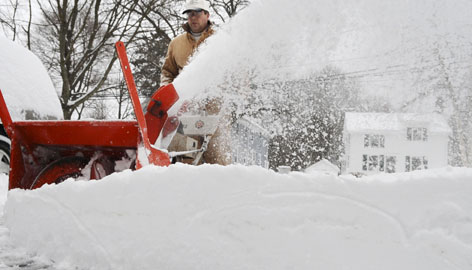 Brian Daniels uses a snow blower to remove snow from his driveway in of Danvers, Mass., Saturday following a winter storm.