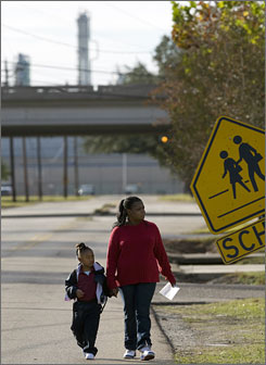 Darlene Patterson walks granddaughter Deondra Scott, 4, near the Wyandotte Early Childhood Center in Baton Rouge, less than half a mile from an ExxonMobil refinery.