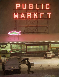 A pedestrian crosses the street near Pike Place Market as heavy snow falls late at night in downtown Seattle, an area which rarely sees such major snow levels.