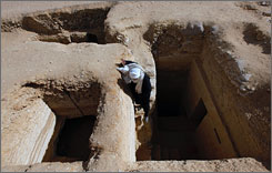 A worker enters one of two newly discovered, 4,300-year-old tombs about 12 miles south of Cairo, on Monday.