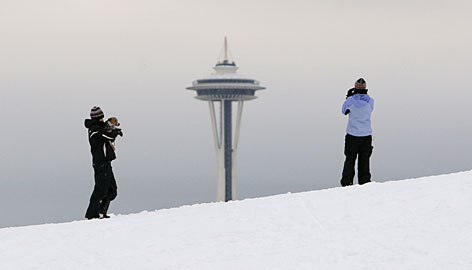 Sisters Lindsey Olson, left, and Diana Olson stop to look at the Space Needle as they walk up a snow covered hill in Seattle on Monday in the aftermath of a weekend storm. Thousands of travelers remained stranded across the Pacific Northwest, but help in Western Washington should arrive in the form of rain by Christmas, the National Weather Service said.