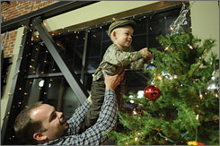 Tony Glasier, 31, helps son Logan, 2, decorate a tree at the 210 Cafe in Visalia, Calif. Facing their own hardship, Tony and his wife, Kathryn, provide the needy with Christmas trimmings.