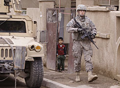 An Iraqi boy looks out of his gate as a U.S. soldier walks by during a routine patrol in Baghdad on Tuesday.