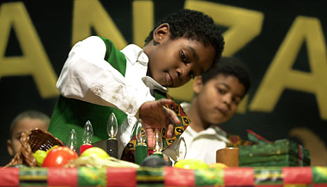 Fifth grade student Iziah Howard, 9, lights a light for the fifth day of Kwanzaa in 2002, as Bertkinzey Marchbanks looks on, at Blenheim Elementary School's Kwanzaa celebration in Kansas City, Mo.