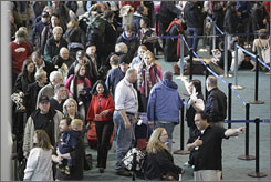 Travelers surround the ticket windows at Portland International Airport Tuesday in Portland, Ore. Flight cancellations on Monday totaled 259, more than a third of the flights that would have flown on an average December Monday, said Kama Simonds, spokeswoman for the Port of Portland.